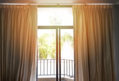 Bedroom window in the morning / sunlight through in room open curtains with balcony royalty free stock photography
