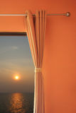 Bedroom windows open and visible sunset at sea. Stock Photography