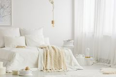 Bedroom with windows. White simple bedroom interior with double bed, knit blanket and windows with curtains royalty free stock images