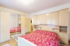 Free Bedroom With Red Blankets And Wooden Wardrobe Royalty Free Stock Photography - 137564687