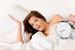 Bedroom - woman with alarm clock wake up Stock Images