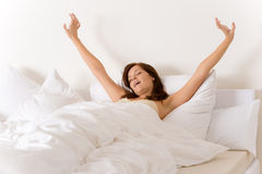 Bedroom - woman waking up and stretching Royalty Free Stock Photos