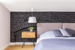 Bed against black brick wall. Bedroom with wooden bedside cabinet with plant next to king-size bed against black brick wall Royalty Free Stock Photo