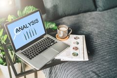 Bedroom,workplace without people,close-up of laptop with inscription analysis on screen on table, desktop. Nearby is newspaper, cup of coffee, notebook. Nobody Royalty Free Stock Images