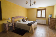 Bedroom in yellow and bricks. Royalty Free Stock Photo