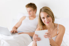 Bedroom - young couple with laptop and book Stock Images
