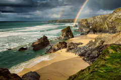 Bedruthan Steps, Cornwall. Double rainbow at Bedruthan Steps, in Cornwall, United Kingdom. Sun setting, with dramatic cliffs, clouds, beach, and sea Royalty Free Stock Photos