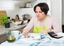 Bedrövliga kvinnliga räknande pengar för betalning Fotografering för Bildbyråer