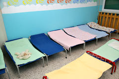 Beds and cots in brightly colored dormitory of a nursery Stock Images