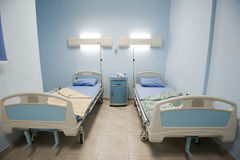 Beds in a private hospital ward. Beds in a small private hospital ward room Stock Photos