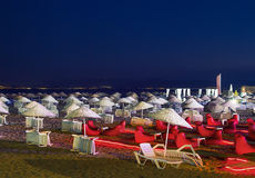 Beds and Straw Umbrellas On A Beach At Night Stock Image