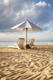 Beds and umbrella on a tropical beach Stock Photos