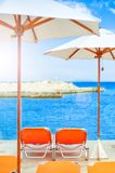 Beds and umbrellas on tropical beach with ocean background. And sun reflection Stock Photo