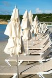 Beds and umbrellas on tropical beach in st johns, antigua. Summer vacation on caribbean. Recreation, leisure, sunbathing, bathing concept Stock Images