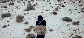 bedsheetmode lägger förföriskt vitt kvinnabarn för foto Flicka i svartkläder i öknen med en bouque Royaltyfri Fotografi