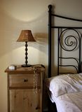 Bedside. Detail of bed and bedside table with lamp Royalty Free Stock Photos