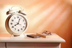 Bedside alarm clock and personal belongings Stock Photos