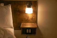 Bedside lamp built into a headboard with a small shelf beneath the lamp stock photo