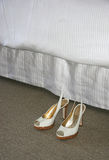 Bedside Shoes. A pair of women's shoes next to a hotel bed royalty free stock photography