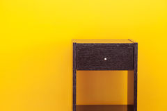 Bedside table. Against a yellow wall in the apartment Stock Image