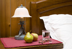 Bedside table. With fruit, glass of water and pills Royalty Free Stock Images