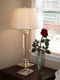 Bedside table. Rose and lamp on a nightstand Royalty Free Stock Photography