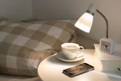Bedside table with fresh coffee, alarm clock, phone and book, co Royalty Free Stock Images