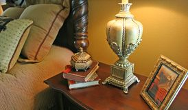 Bedside Table and Lamp. Mahogany bedside table with ornate base of Stock Photography