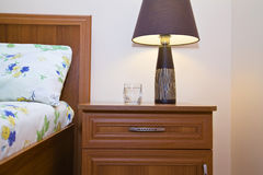 Bedside table with lamp glowing  closeup Stock Image