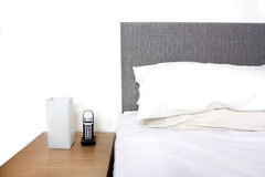 Bedside table with lamp and phone Royalty Free Stock Photography