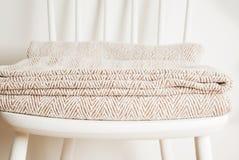 Bedspread lub koc na białym rocznika krześle, minimalistic styl housekeeping kosmos kopii obraz stock