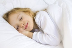 Bedtime. Little blond girl wearing white blouse in white bedchlothes Royalty Free Stock Images