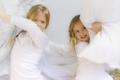 Bedtime. Little blond girl wearing white blouse in white bedchlothes Royalty Free Stock Photo