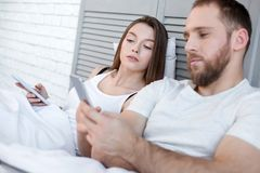 Serious woman looking what her man typing on his phone. Bedtime. Beautiful serious unsmiling dark-haired women holding her phone and looking what her men typing Royalty Free Stock Image