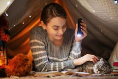 Before bedtime. A girl with a Scottish and British cat reading a book in a tent. A concept of rest, fairy tales, night, sleep and royalty free stock photography