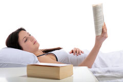 Bedtime reading. A young woman lying in her bed reading a book. All on white background Stock Images