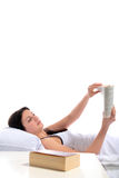 Bedtime reading. A young woman lying in her bed reading a book. All on white background Stock Image