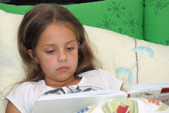 Bedtime reading. Young girl reads book in bed Royalty Free Stock Photos