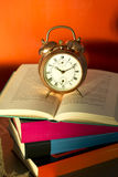 Bedtime reading, alarm clock and books Stock Images