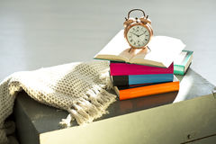 Bedtime reading, alarm clock and books Royalty Free Stock Image