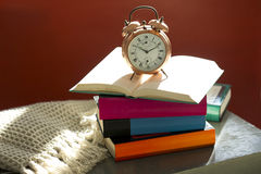 Bedtime reading, alarm clock and books on bedside table Royalty Free Stock Photography