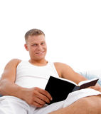 Bedtime reading in bed a book. Man enjoying reading in bed on white background Royalty Free Stock Photos