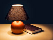 Bedtime reading - lamp with book at night. Real lamplight - hence shadows Royalty Free Stock Photography