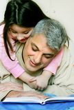 Bedtime story. Happy father holding his smiling sweet six year old daughter on his back, while he reads her a bedtime story Stock Photo