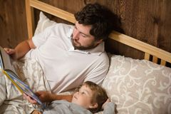 Bedtime Story. Dad and daughter read a book. Royalty Free Stock Photos