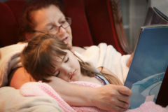 Bedtime Story with Grandma. Cute little girl falling aspleep in her Grandma's arms as Grandma reads a bedtime story Royalty Free Stock Images