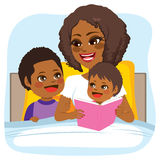 Bedtime Story Reading. Young African American mother reading bed time tale story to son and daughter on bed Royalty Free Stock Image