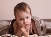 Bedtime  (young girl lying on the bed under the covers) Royalty Free Stock Image