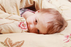 Bedtime  (young girl lying on the bed under the covers) Stock Photography