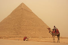 Beduíno em um camelo perto da pirâmide de Khafre em um strom da areia, o Cairo Fotografia de Stock Royalty Free